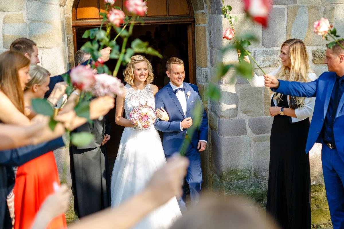 Die Gäste empfangen das Brautpaar vor der Kirche mit Rosen