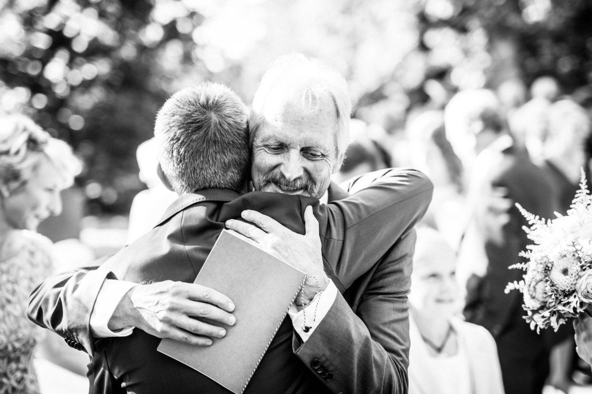 Der Vater der Braut schließt seinen Schwiegersohn in die Arme
