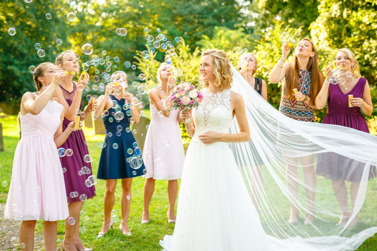 Die Braut steht in Mitten von Seifenblasen, den ihre Brautjungfern machen