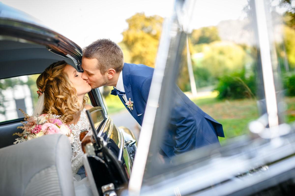 der Bräutigam küsst seine Braut, die im Brautauto sitzt