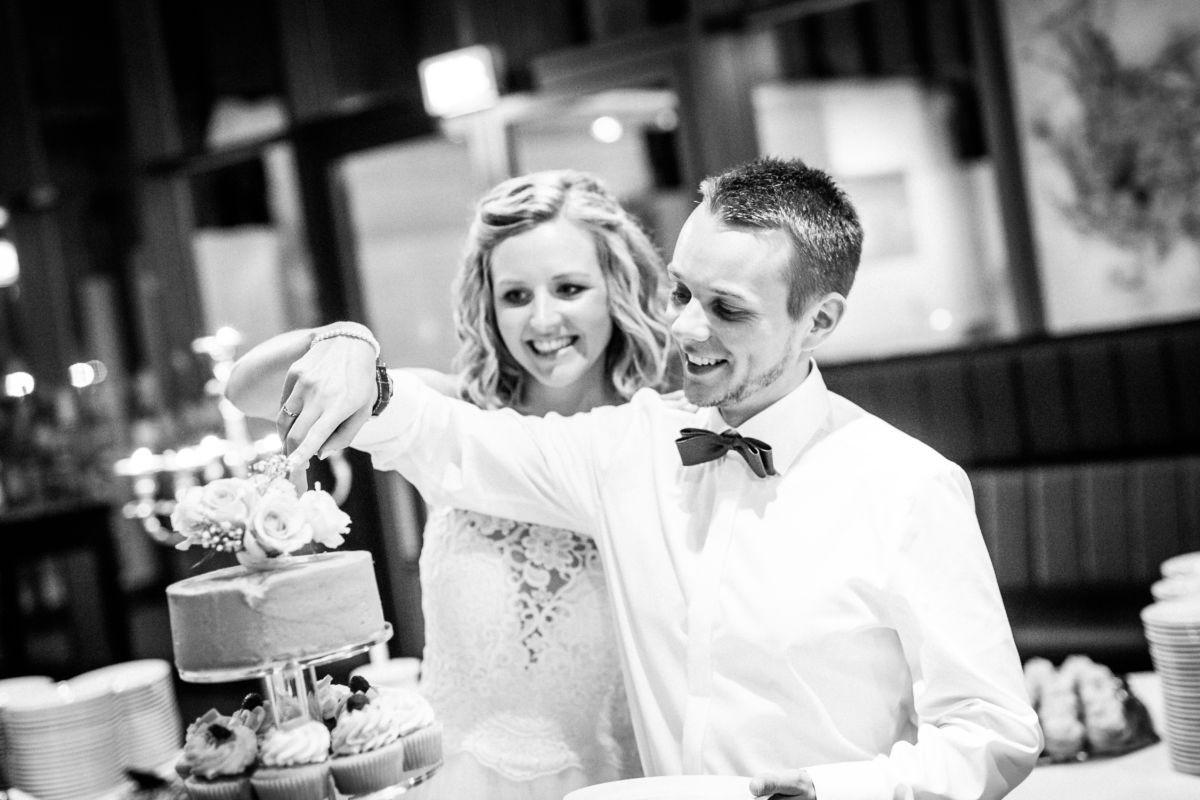Brau und Bräutigam schneiden die Hochzeitstorte an