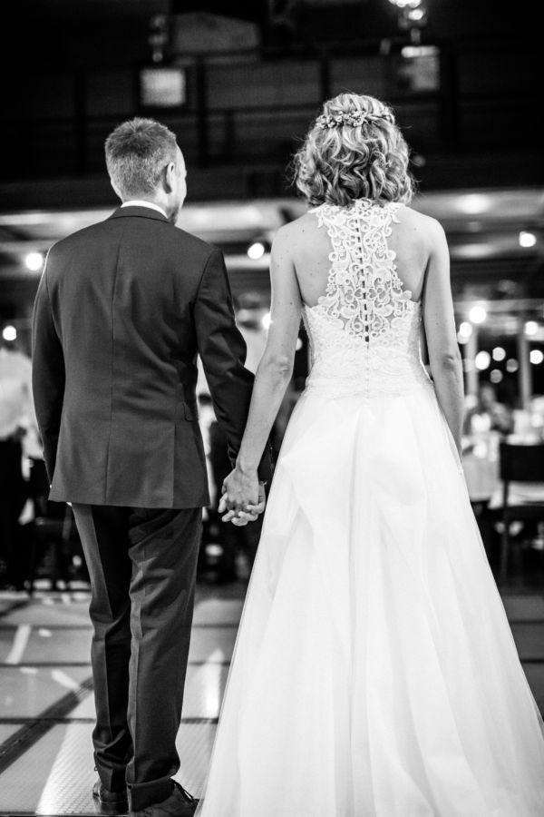 Hier sind Braut und Bräutigam auf ihrem Hochzeitsfest von hinten zu sehen