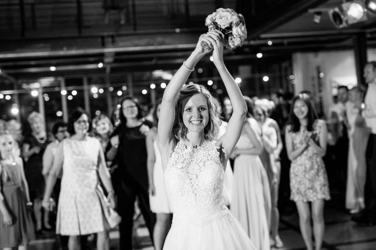 Der Brautstrauß wird geworfen und die Braut strahlt in die Kamera