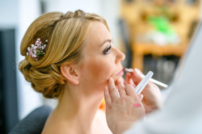 Die Lippen der Braut werden für die Hochzeit geschminkt.