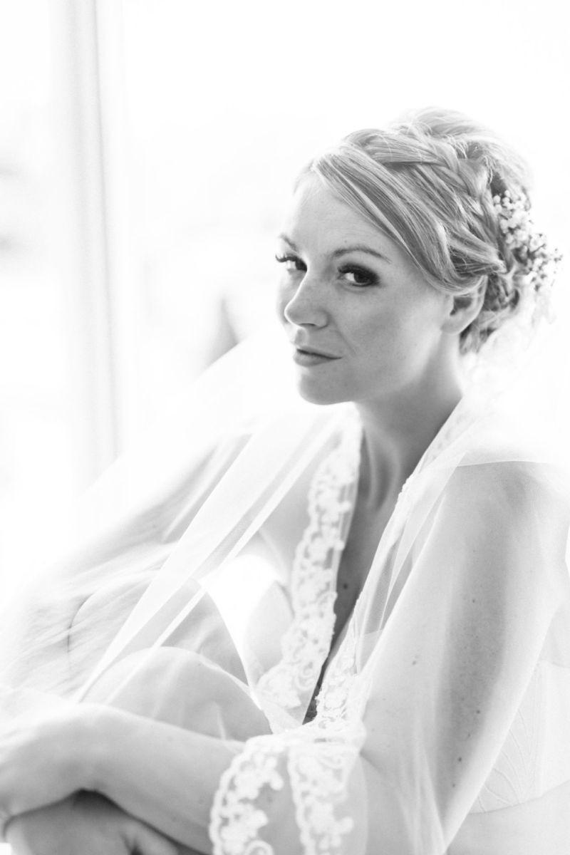 Beim Getting Ready nehmen wir hochzeitsfotografen Mettmann uns die Zeit auch schöne und stilvolle Bilder in Unterwäsche zu schießen. Hier sitzt die Braut mit den Beinen angezogen, verhüllt von ihrem langen Schleier.