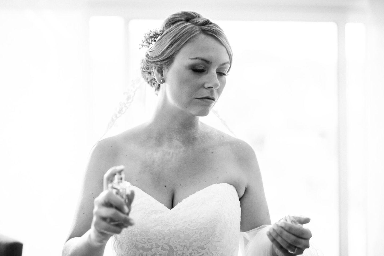 Die Braut besprüht sich mit Parfüm.