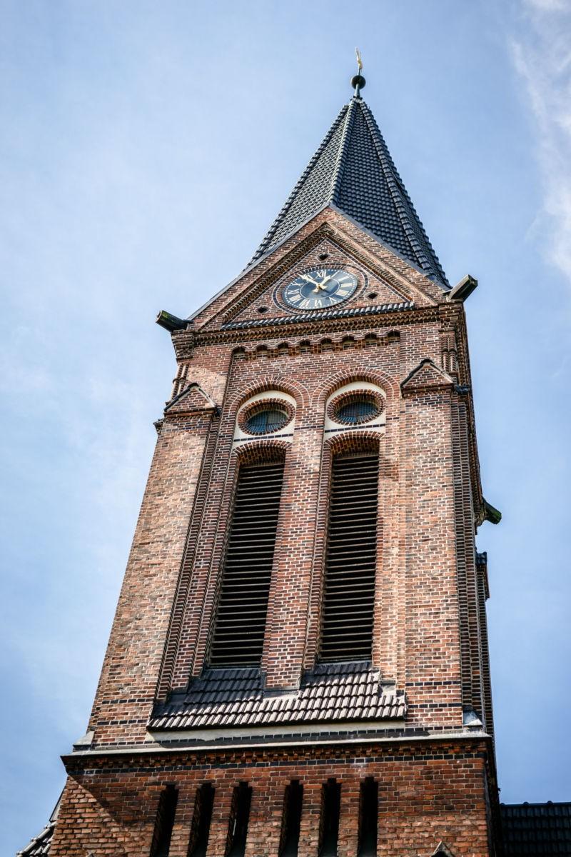 Der Kirchturm ragt in den blauen Himmel