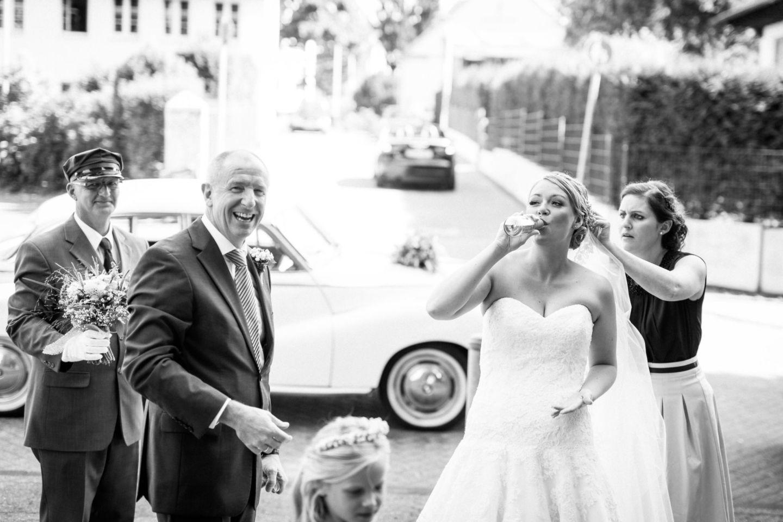 Die Braut steht vor der Kirche und trinkt sich Mut an während die Trauzeugin letzte Handgriffe an der Frisur macht