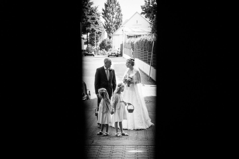 die Braut und der Brautvater stehen gemeinsam mit den Blumenmädchen vor der Kirchentür
