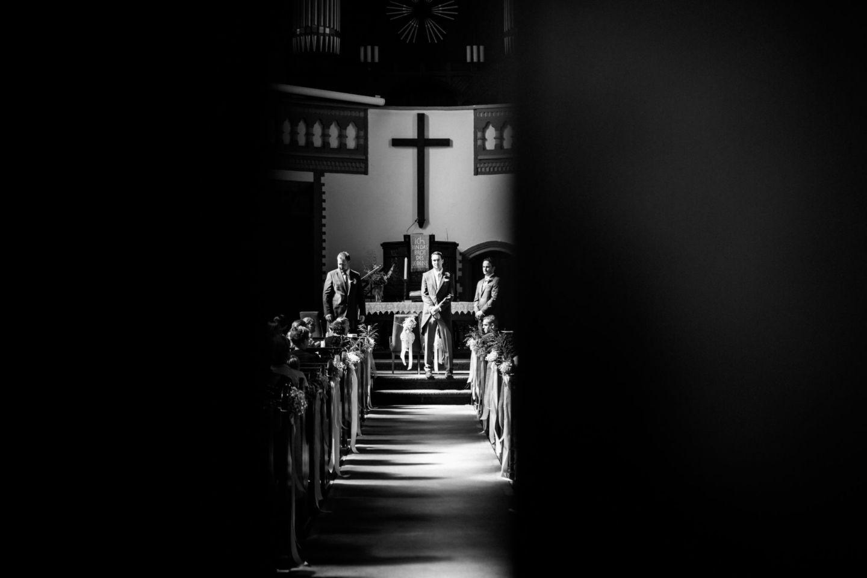 Der Bräutigam steht vor dem Altar und schaut seiner Braut sehnsuchtsvoll entgegen