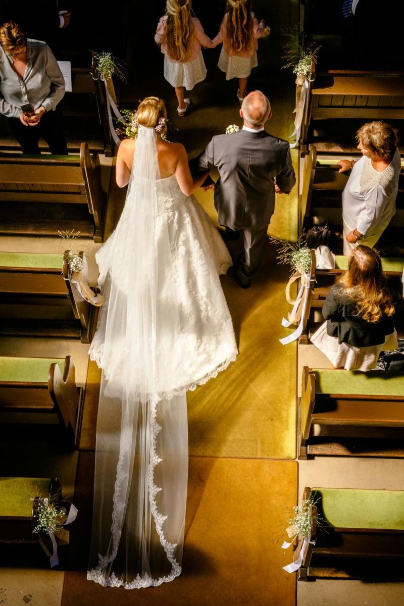 die Braut und der Brautvater schreiten zum Altar und sind von oben fotografiert.