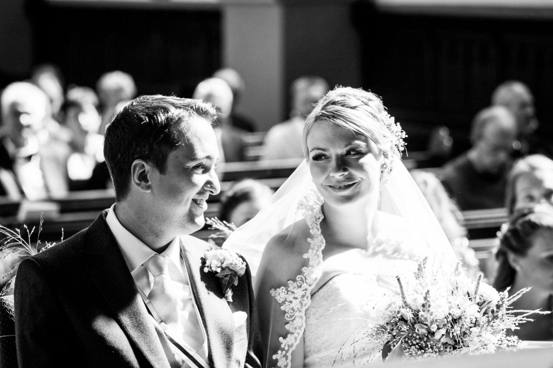 Braut und Bräutigam sitzen am Altar und schauen sich verliebt an