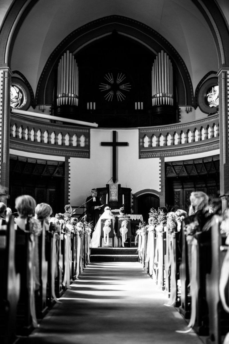 Die Kirchengemeinde mit Braut und Bräutigam sind von hinten fotografiert