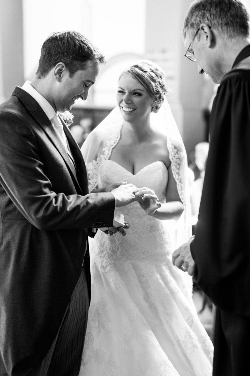 Braut und Bräutigam tauschen die Eheringe