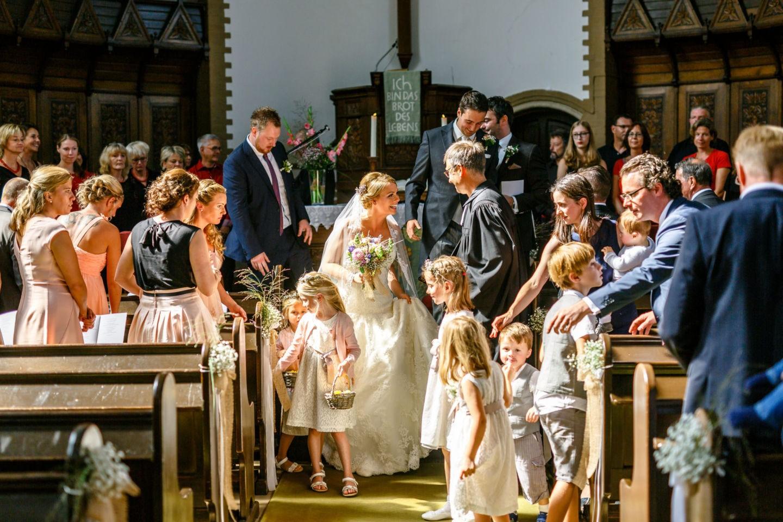 die Hochzeitsgemeinschaft schreitet in gelöster Stimmung aus der Kirche
