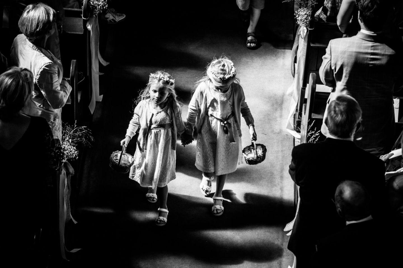 Die Blumenmädchen gehen Hand in Hand den Kirchengang entlang und wurden vom Hochzeitsfotografen Mettmann von oben fotografiert