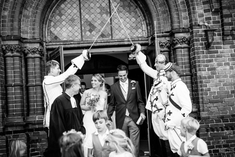 Braut und Bräutigam werden an der Kirchen tür von Fechtern erwartet
