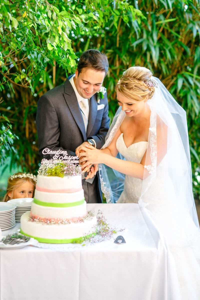 Braut und Bräutigam schneiden ihr Hochzeitstorte an