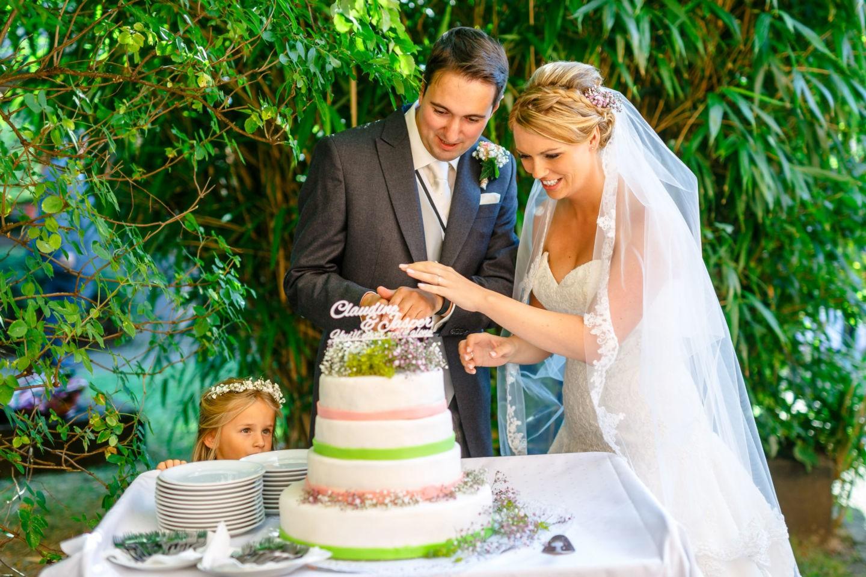 Braut und Bräutigam schneiden ihre Hochzeitstorte an