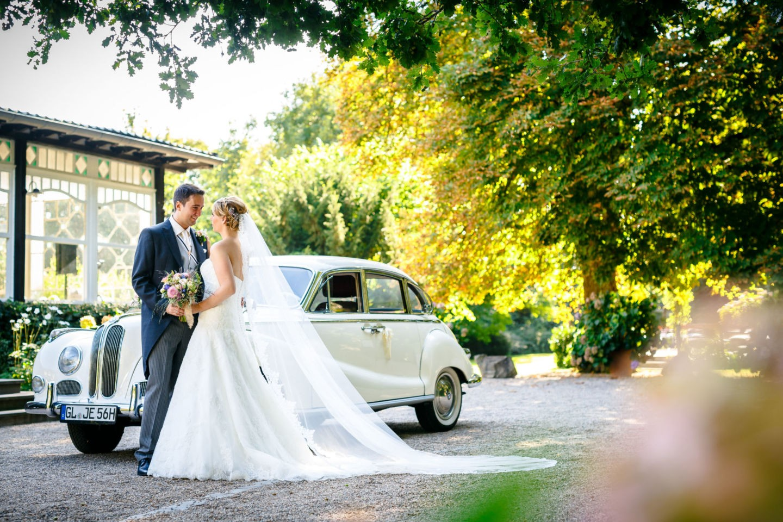 Braut und Bräutigam stehen vor dem Brautauto und sehen sich verliebt an