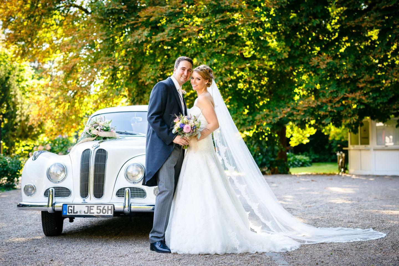 Braut und Bräutigam stehen vor dem Brautauto uns blicken in die Kamera