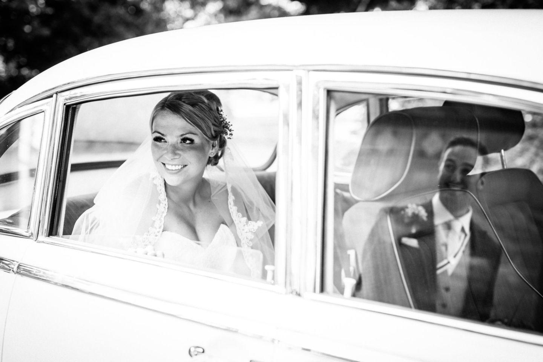 Die Braut sitzt im Brautauto und strahlt ihren Bräutigam an, welcher sich in der Autoscheibe spiegelt