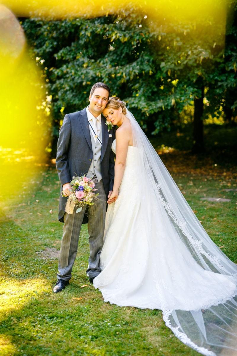 Die Braut lehnt sich an ihren Bräutigam und hat die Augen geschlossen