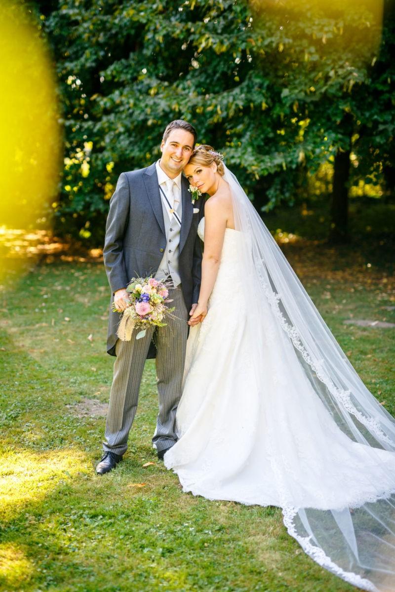 Die Braut schmiegt sich an ihren Bräutigam und beide sehen in die Kamera