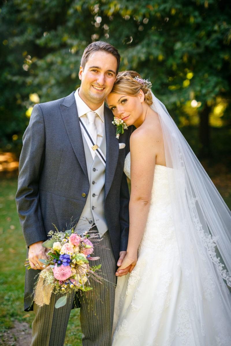 Brautpaarshooting in Mettmann, Braut und Bräutigam sehen ind ie Kamera