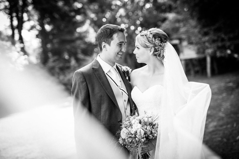 Braut und Bräutigam sehen sich an, der Schleier weht in die Kamera