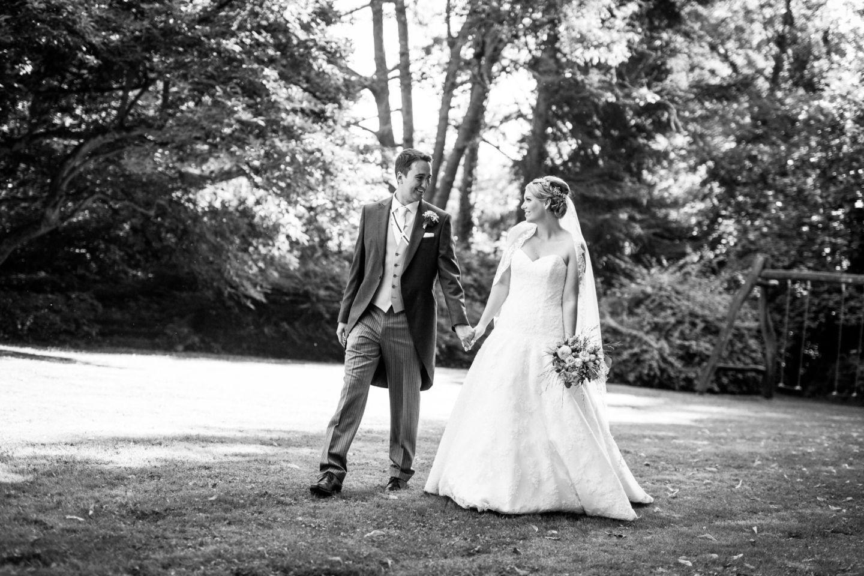 Braut und Bräutigam schlendern Hand in Hand über eine Wiese und sehen sich an