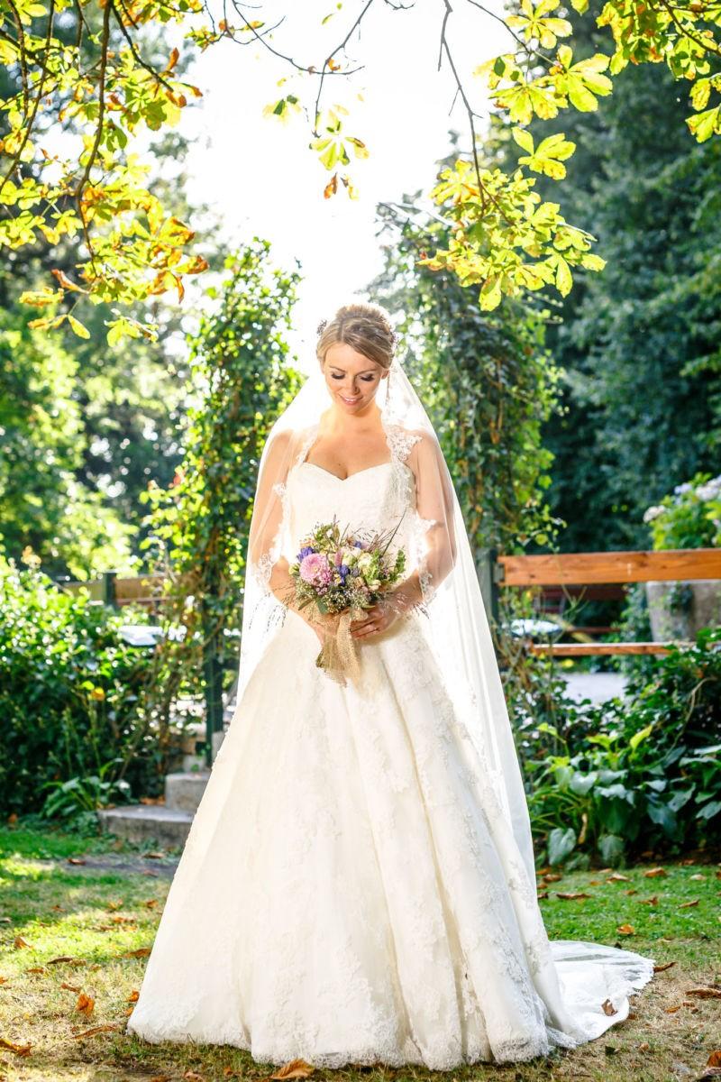 Die Braut sieht auf ihren Brautstrauß