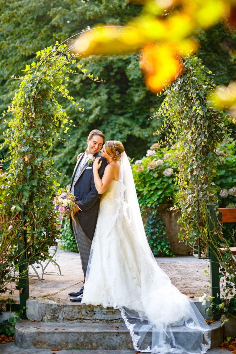 Die Braut steht hinter dem Bräutigam, beide strahlen sich an