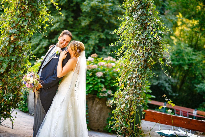 die Braut steht hinter dem Bräutigam, beide sehen sich an