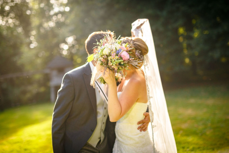 Braut und Bräutigam küssen sich und halten den Brautstrauß in die Kamera