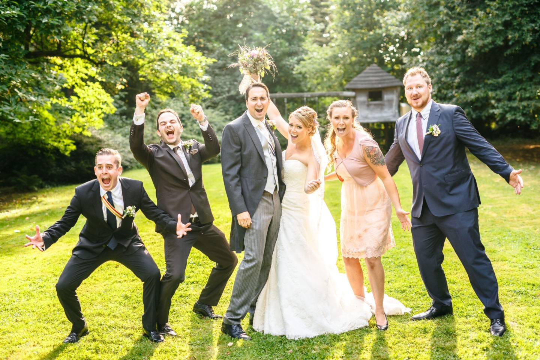 Das Brautpaar ist umgeben von seinen Trauzeugen. Alle machen Spaß ind ie Kamera.