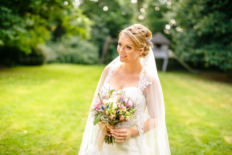 Die Braut steht in ihrem weeißen Kleid mit dem Schleier und dem Brautstrauß da und sieht besinnlich in die Ferne