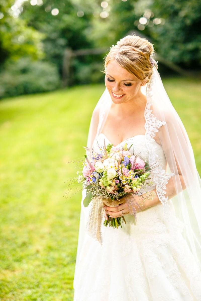 Portrait der Braut. Sie schaut auf ihren Brautstrauß