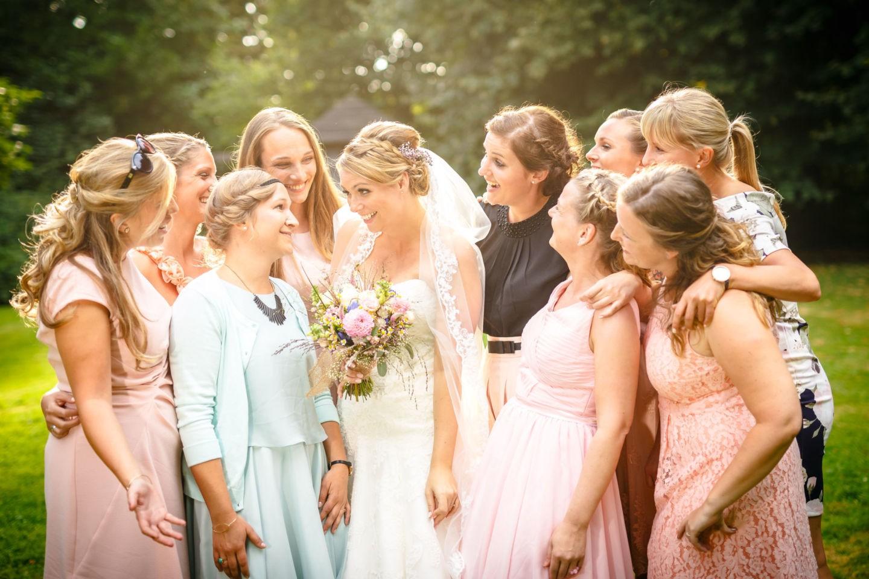 Die Braut ist umgeben von ihren Brautjungfern. Alle lachen sich an.