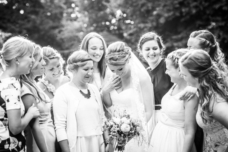 Die Braut ist umgeben von ihren Freundinnen. Alle lachen sich an.
