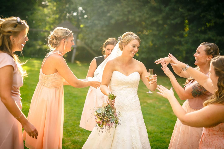 Die Braut trinkt ein Glas Champagner und wird von ihren Brautjungfern angefeuert.