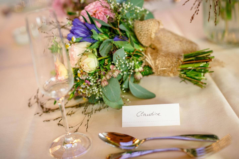 das Namenskärtchen der Braut liegt neben dem Brautstrauß auf dem Tisch