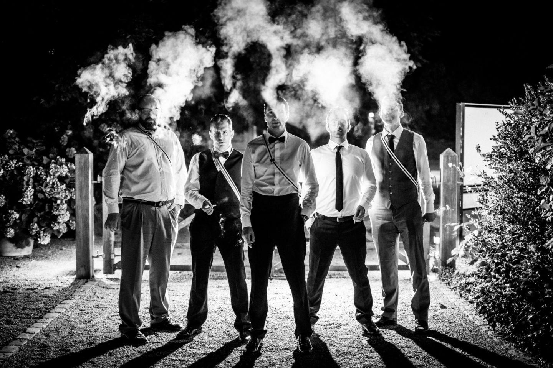 der Bräutigam steht mit seinen Trauzeugen im Dunkeln und raucht Zigarre, sodass der Rauch hinauf zieht