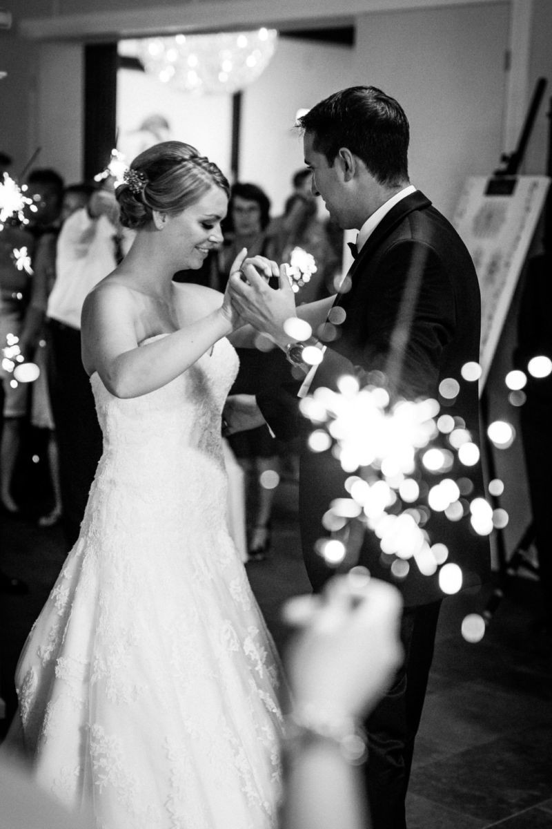 Das Brautpaar tanzt den ersten Tanz. Die Gäste haben Wunderkerzen angezündet.