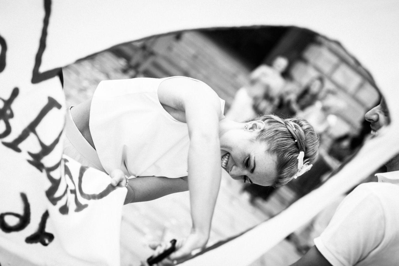 Die Braut schneidet ein riesiges Herz aus einem Bettlaken aus.