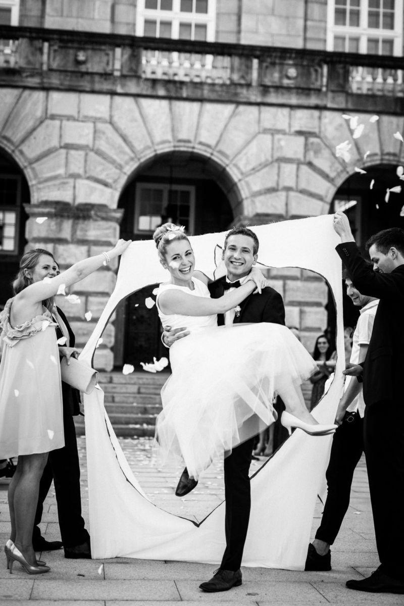 der Bräutigam trägt seine Braut durch das zuvor ausgeschnittene Herz vor dem Standesamt in Mülheim und der Hochzeitsfotograf NRW macht die Hochzeitsfotos
