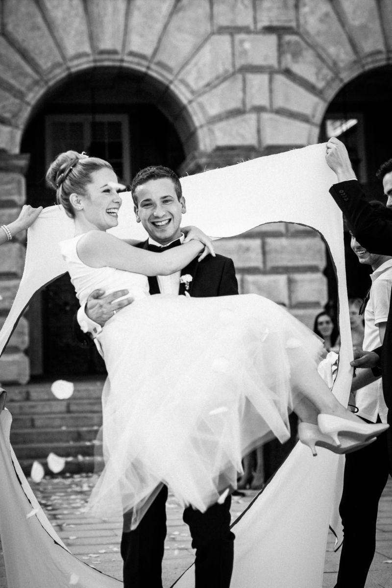 Der Bräutigam hat seine Braut auf den Armen und lächelt ind ie Kamera des Hochzeitsfotografen Mülheim an der Ruhr