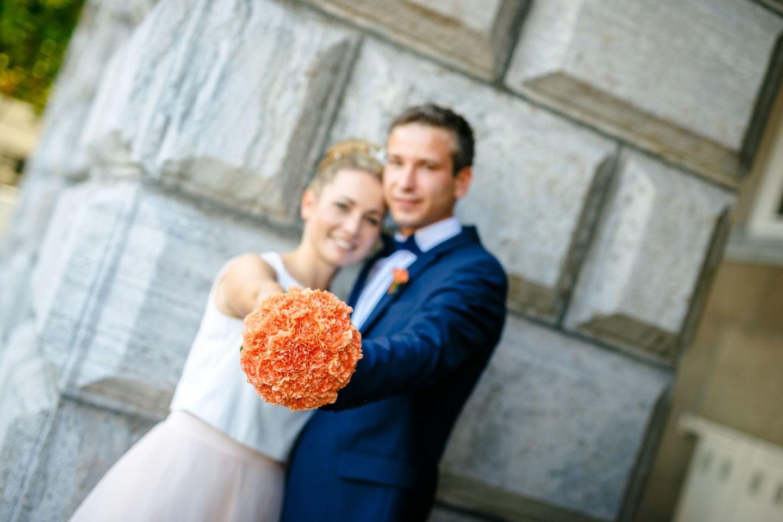 das Brautpaar hält den Brautstrauß in die Kamera des Hochzeitsfotografen