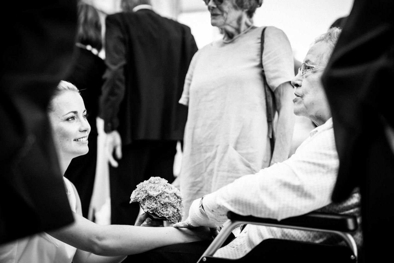 die Braut hält die Hand ihrer im Rollstuhl sitzenden Großmutter
