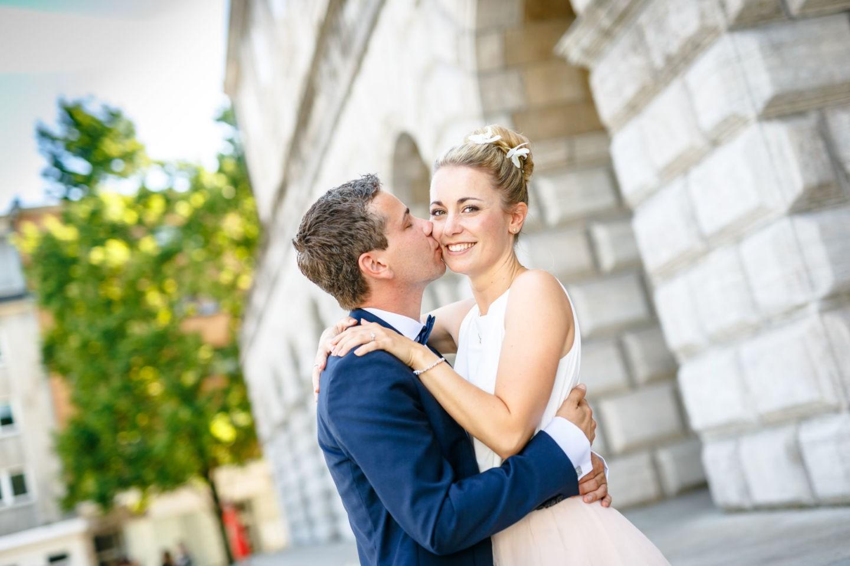 die Braut strahlt in die Kamera des Hochzeitsfotografen NRW während der Bräutigam sie auf die Wange küsst